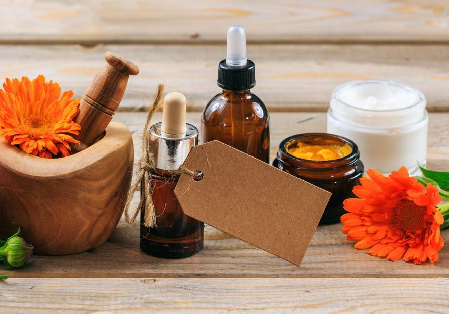 Calendula or pot marigold aromatherapy. Essential oil and cosmetics, fresh blooming twig in a mortar, blank tag, banner. Wooden table background